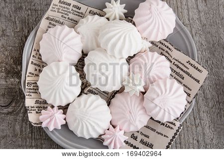White and pink marshmallows on vintage paper in dish. Top view.