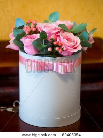 Beautiful bouquet of pink roses or blossoming flowers in white gift box decorated with silk ribbon bow indoors on wooden background