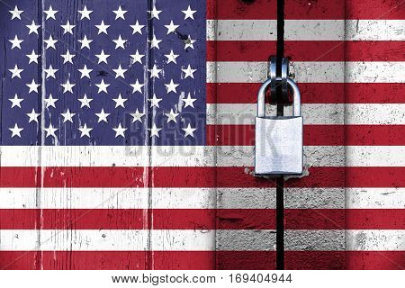 United states of america flag on a wooden door locked with a padlock concept background with copy space