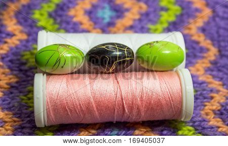 Multi-colored beads and thread spool on the knitted background.