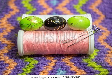 Multi-colored beads, spools of thread and tailor's pins on the knitted background.