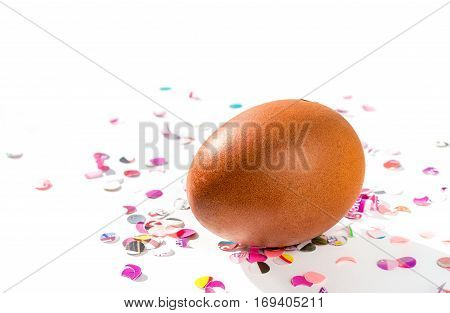 Brown chicken egg with shadow and colorful confetti on a white background.