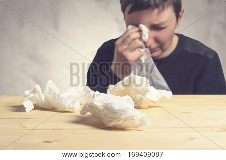 Sad woman crying wiping her tears. Selective focus on wipes on wooden table.