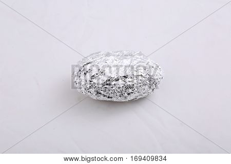 aluminum foil wrapped baked potato. isolated on white with room for your text.