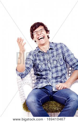 Young hispanic man wearing glasses, blue shirt with rolled up sleeves and jeans sitting on chair with hand near his face and loudly laughing isolated on white background - fun concept