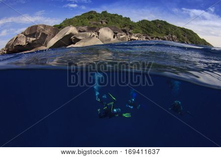 Scuba divers underwater with island