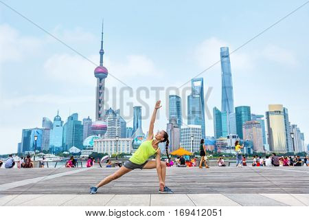 Active city lifestyle fitness woman health goal. Yoga teacher training outside on the Bund, Shanghai. Healthy living girl doing exercise with extended side angle pose in summer outdoors.