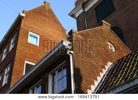 Stone buildings of Amsterdam on a background of blue sky