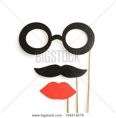 Fake lips, glasses and mustaches on sticks. Isolated on white background.