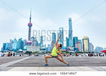 Yoga fitness instructor in urban city outdoors in Shanghai, China. Sport woman in exalted warrior pose 4 doing workout class on the Bund boardwalk. Female yogi.