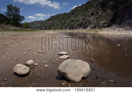 Some boulders and rocks along the Colorado River in Texas in low water dry conditions in springtime