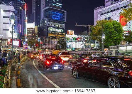 TOKYO, JAPAN - NOVEMBER 12, 2016: Cars in traffic at Shibuya district in Tokyo, Japan. Shibuya road cross is one of the busiest crosswalks in the world.