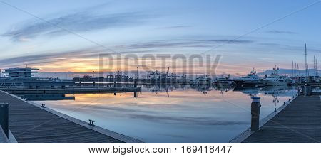 First rays of sun peeking over the horizon. Port twilight in the Valencia harbor cranes working loading transport ships, red and blue skyline reflected in water. gigapan