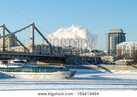 Moscow, Russia - January 8, 2017: Pleasure boat sailing on a frozen river under the bridge metal structures frosty sunny winter day on the background of residential and office buildings and power plant pipes spewing steam - in Moscow Russia