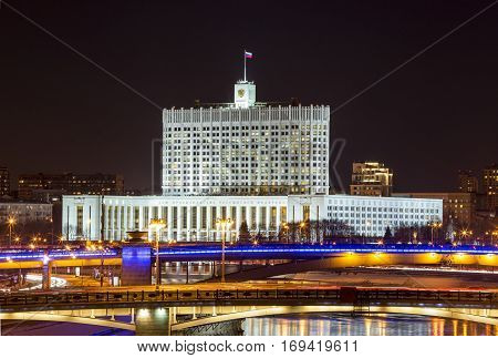 Night winter panorama of the House of Government of Russian Federation road and metro bridges across the Moscow River. Rich illumination and reflection in the river.