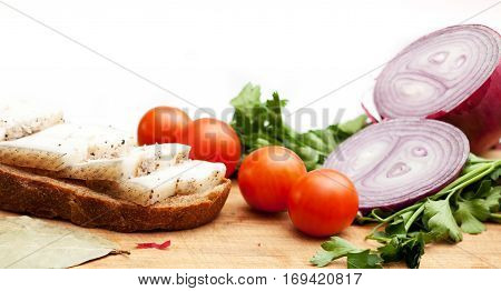 Lard on bread tomatoes onions fresh and herbs on a white background