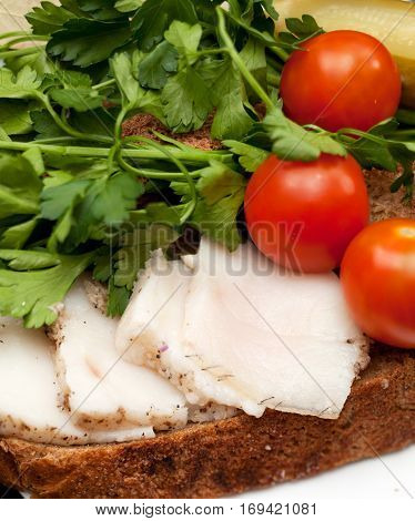 Lard on bread tomatoes and fresh herbs on the table