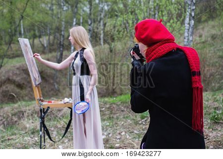 Long-haired girl in the lens of the camera artist paints in oils on canvas self portrait. Easel outdoors. The girl photographer photographing the artist in the process of working on a painting. Plein Air. The work of the artist and photographer