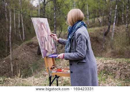 The girl young artist paints a picture in oil on the plein Air . Painting lesson in nature . Blonde draws a self-portrait in the spring forest . Brush on canvas