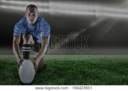 Portrait of rugby player kneeling and holding ball against spotlightand copy space 3d