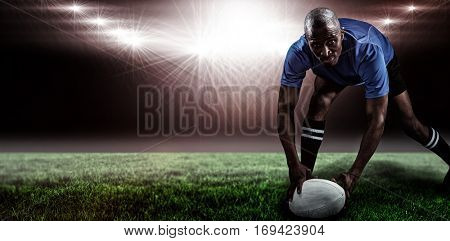 Portrait of sportsman bending and holding ball while playing rugby against spotlight and copy space 3d