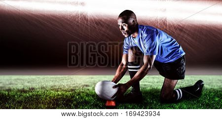 Rugby player looking away while keeping ball on kicking tee against spotlight and copy space 3d