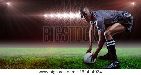 Portrait of rugby player holding ball against spotlight and copy space 3d