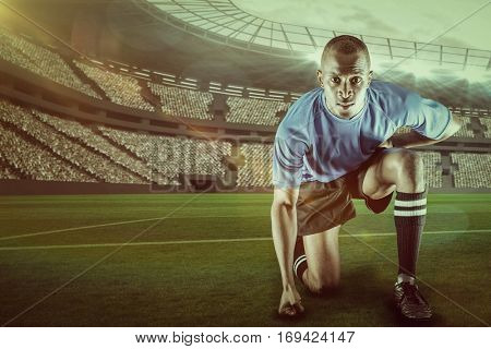Portrait of confident sportsman kneeling against rugby stadium with copy space 3d