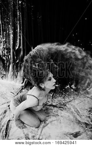 Girl Dancer Jumping And Dancing In The White Dust With Flour On A Black Background. Studio Shot Of W