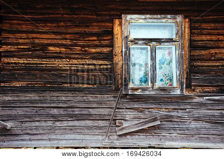 small window on an old wooden house that is falling apart