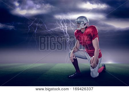 American football player looking away while kneeling against stormy dark sky with lightning bolts with copy space 3d