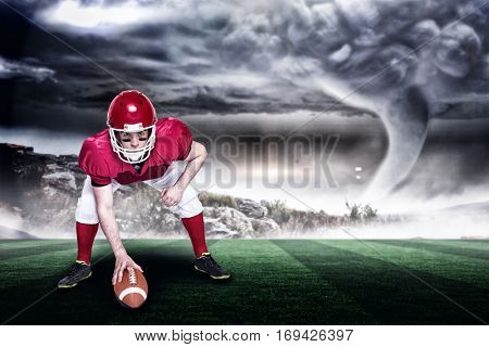American football player in attack stance against stormy sky with tornado over landscape with copy space 3d