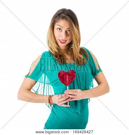 Beautiful woman holding red heart-shaped lollypop in front of her isolated on white