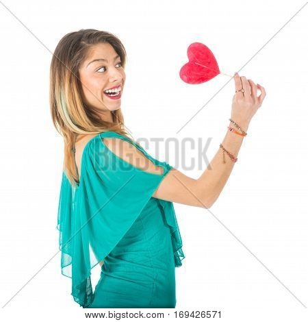 Sideview of beautiful woman holding red heart-shaped lollypop in front of her isolated on white
