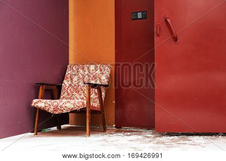 Old armchair discarded at entrance door in purple and burgundy colors copyspace
