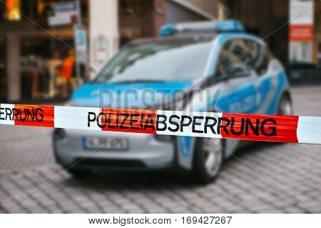 Police tape at the crime scene. Focus on the police tape, a police car on blurred background. german police.