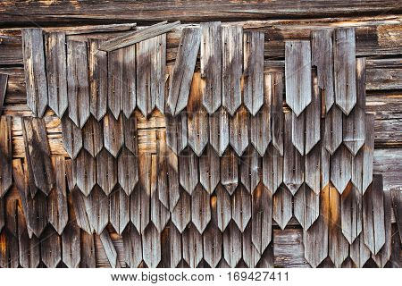 ancient wall covering on an old wooden house that is falling apart