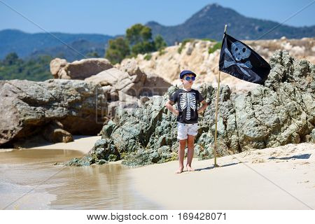 Cute boy dressed as pirate on tropical beach during summer holiday vacation