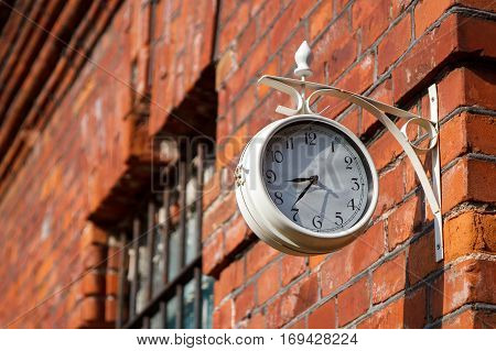 A white street clock by a brick wall