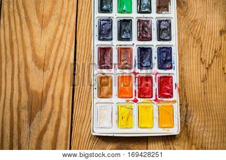 High watercolor paints on wooden background. Solid watercolor in tiles. Tool to perform drawing work .Tools for drawing students artists. A set of warm and cool colors. Vintage texture. Solid watercolor in tiles. Tool to perform drawing work
