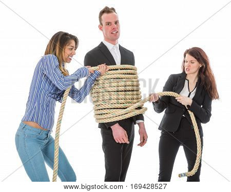 Two angry woman tying a business man with rope isolated on a white background