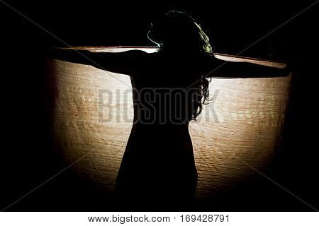 Silhouette of woman in backlight behind a kerchief