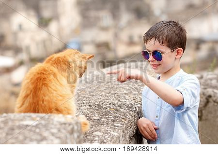 Cute little boy met a cat while walking at typical italian town  during summer holiday vacation