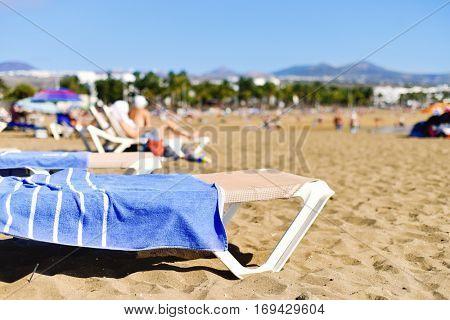unrecognizable people sunbathing at the Playa de Matagorda beach in Puerto del Carmen, Lanzarote, in the Canary Islands, Spain