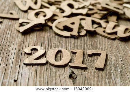 closeup of some wooden numbers forming the number 2017, as the new year, on a rustic wooden table next to a pile of wooden letters