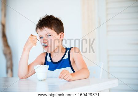 Portrait of cute little boy refuses to eat delicious yogurt