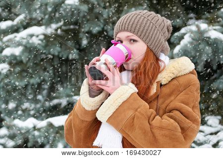 beautiful woman drinking a hot drink and keep warm on winter outdoor, snowy fir trees in forest, long red hair, wearing a sheepskin coat