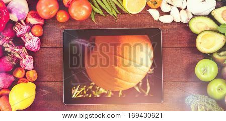 Digital tablet surrounded with fresh vegetables against pumpkin patch