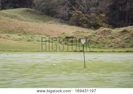 Putting practice green on golf course with pole and golf ball near hole