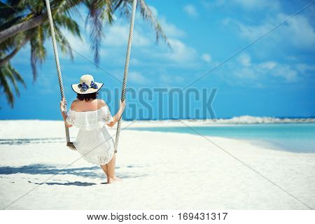 Beautiful woman swinging with tropical beach on background on Koh Phangan island. Thailand, Asia